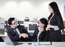Businesspeople shaking hands in office room Royalty Free Stock Photos
