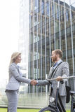Businesspeople shaking hands outside office building Stock Photo