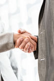Businesspeople shaking hands over a blurred abstract background Royalty Free Stock Photos
