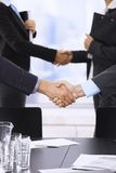 Businesspeople shaking hands. In skyscraper office on meeting stock photo