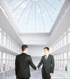 Businesspeople shaking hands. Two handsome businesspeople shaking hands in modern spacious interior. Partnership concept. 3D Rendering Royalty Free Stock Image