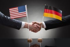 Businesspeople shaking hands with us and germany flags Royalty Free Stock Photography