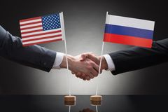 Businesspeople shaking hands with us and russia flags Royalty Free Stock Photography