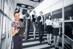Businesspeople showing sign of okay. Business women stands foreground with blurred businesspeople showing sign of okay Royalty Free Stock Photo