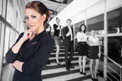 Businesspeople showing sign of okay. Business women stands foreground with blurred businesspeople showing sign of okay Royalty Free Stock Images