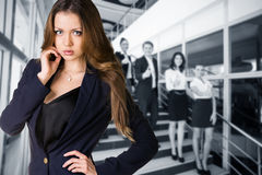 Businesspeople showing sign of okay. Business women stands foreground with blurred businesspeople showing sign of okay Royalty Free Stock Photography