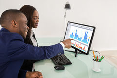 Businesspeople Showing Their Success Teamwork. African American Business Man And Woman Showing Their Successful Teamwork On Computer Royalty Free Stock Image