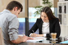 Businesspeople signing contracts after deal Stock Images