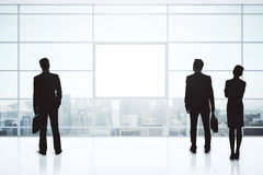 Businesspeople silhouettes and blank poster Royalty Free Stock Photo