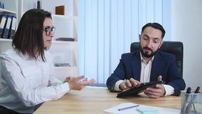 Businesspeople sit and have informal meeting looking at data on digital tablet together stock footage