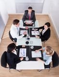 Businesspeople sitting at conference table Stock Images