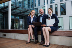 Businesspeople sitting with laptop in office premises. Portrait of businesspeople sitting with laptop in office premises Stock Photos