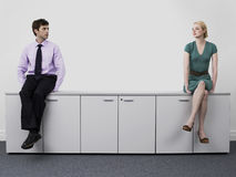 Businesspeople sitting on office cabinets Stock Images