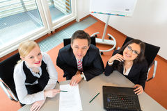Businesspeople are sitting at office desk stock photography