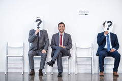 Businesspeople sitting in queue and waiting for interview, holding question marks in office Stock Photography