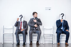 Businesspeople sitting in queue and waiting for interview, holding question marks in office Stock Photos