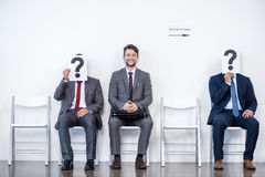 Businesspeople sitting in queue and waiting for interview, holding question marks in office. Business concept stock photo