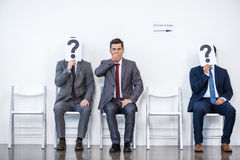 Businesspeople sitting in queue and waiting for interview, holding question marks in office Royalty Free Stock Photo