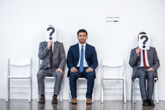 Businesspeople sitting in queue and waiting for interview, holding question marks in office Royalty Free Stock Images