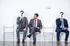 Businesspeople sitting in queue and waiting for interview, holding question marks in office Royalty Free Stock Photos