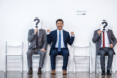 Businesspeople sitting in queue and waiting for interview, holding question marks in office Royalty Free Stock Photography