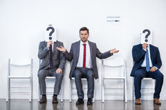 Businesspeople sitting in queue and waiting for interview, holding question marks in office. Business concept royalty free stock images