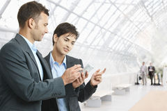 Businesspeople with smartphone. Two businesspeople standing in hallway, looking at mobile phone, smiling royalty free stock image