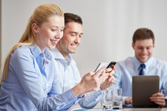 Businesspeople with smartphones and tablet pc. Business, people, technology and teamwork concept - smiling businesspeople with smartphones and tablet pc computer Stock Image