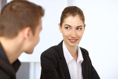 Businesspeople smiling each other. Young happy businessman and businesswoman sitting at table in office and smiling each other Stock Image