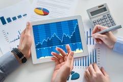 Businesspeople som analyserar grafen med den Digital minnestavlan Royaltyfri Fotografi