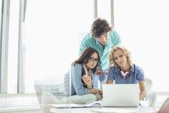 Businesspeople som använder bärbara datorn på tabellen i idérikt kontor Royaltyfri Fotografi