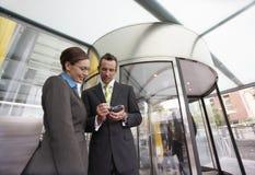 Businesspeople som använder PDA i Front Of Revolving Door Arkivbilder