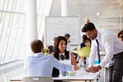 Businesspeople som arbetar på skrivbord i modernt kontor arkivfoton