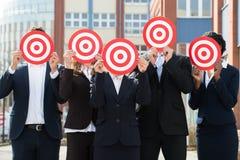 Businesspeople som döljer framsidan med darttavlan royaltyfri bild