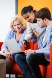Businesspeople som diskuterar över bärbara datorn i lobby Royaltyfria Bilder