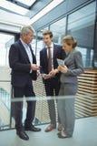 Businesspeople som diskuterar över elektroniska apparater i passagen royaltyfri foto