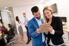Businesspeople som diskuterar, medan genom att anv?nda den digitala minnestavlan i regeringsst?llning fotografering för bildbyråer
