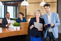 Businesspeople som diskuterar på kontorslobbyen Arkivfoto