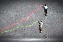 Businesspeople som drar diagram på väggen Arkivfoto