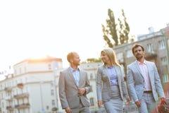 Businesspeople som går i stad på solig dag Royaltyfri Bild