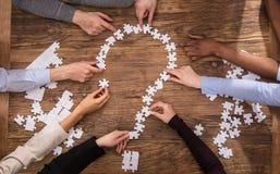Businesspeople som gör frågan Mark Sign With Jigsaw Puzzle Arkivfoto