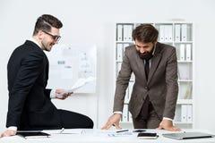 Businesspeople som gör skrivbordsarbete och att skratta Arkivbild