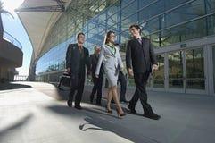 Businesspeople som går förbi kontorsbyggnad Fotografering för Bildbyråer