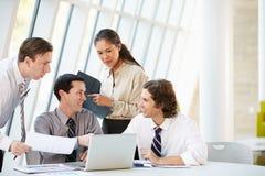 Businesspeople som har möte bordlägger omkring, i modernt kontor Royaltyfri Bild