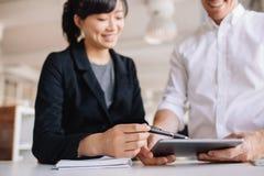 Businesspeople som i regeringsställning använder pekskärmdatoren fotografering för bildbyråer