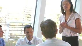 Businesspeople som placeras runt om tabellen som har möte arkivfilmer