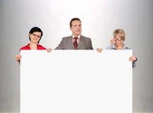Businesspeople som rymmer den tomma affischen Arkivfoton