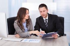 Businesspeople som ser skrivplattan som arbetar på kontorsskrivbordet Arkivbild