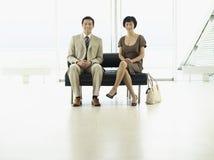 Businesspeople som sitter på flygplatslobbyen royaltyfri bild