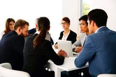 Businesspeople som sitter på tabellen fotografering för bildbyråer